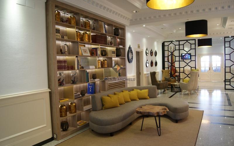 libreria en hotel, con iluminacion y baldas doradas